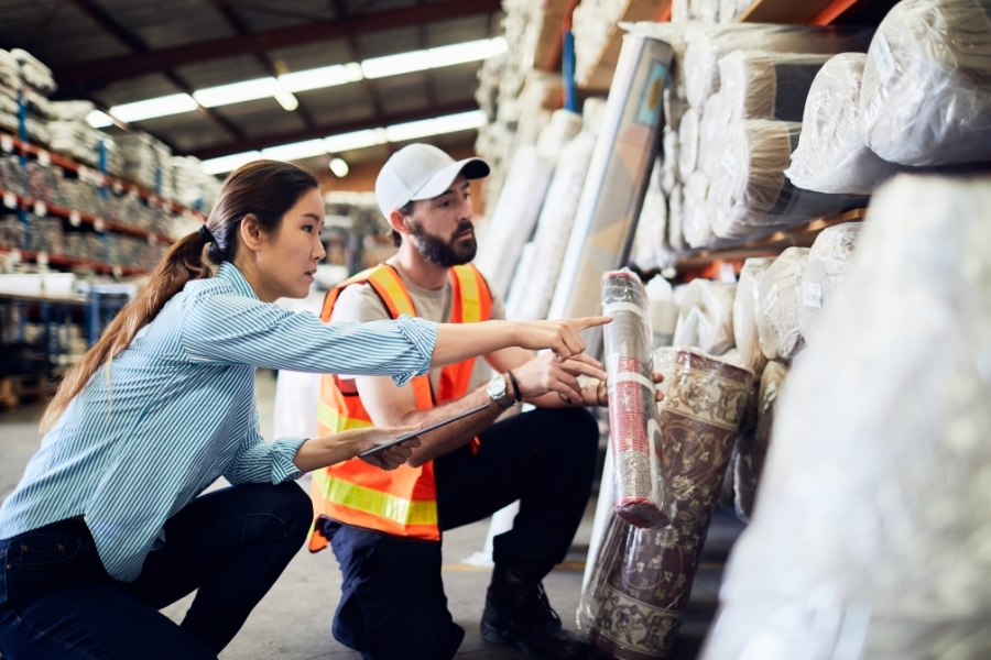 Asian woman crouching with a clipboard next to a white man with a beard wearing a safety vest and holding a small rolled up rug. The woman is pointing to rugs stacked in industrial shelving in a warehouse and the man is looking where she is pointing.