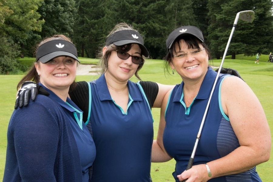 Three women in matching blue golf shirts with black visors with their arms around each other facing the viewer smiling with the far right woman holding a golf iron resting on her shoulder.