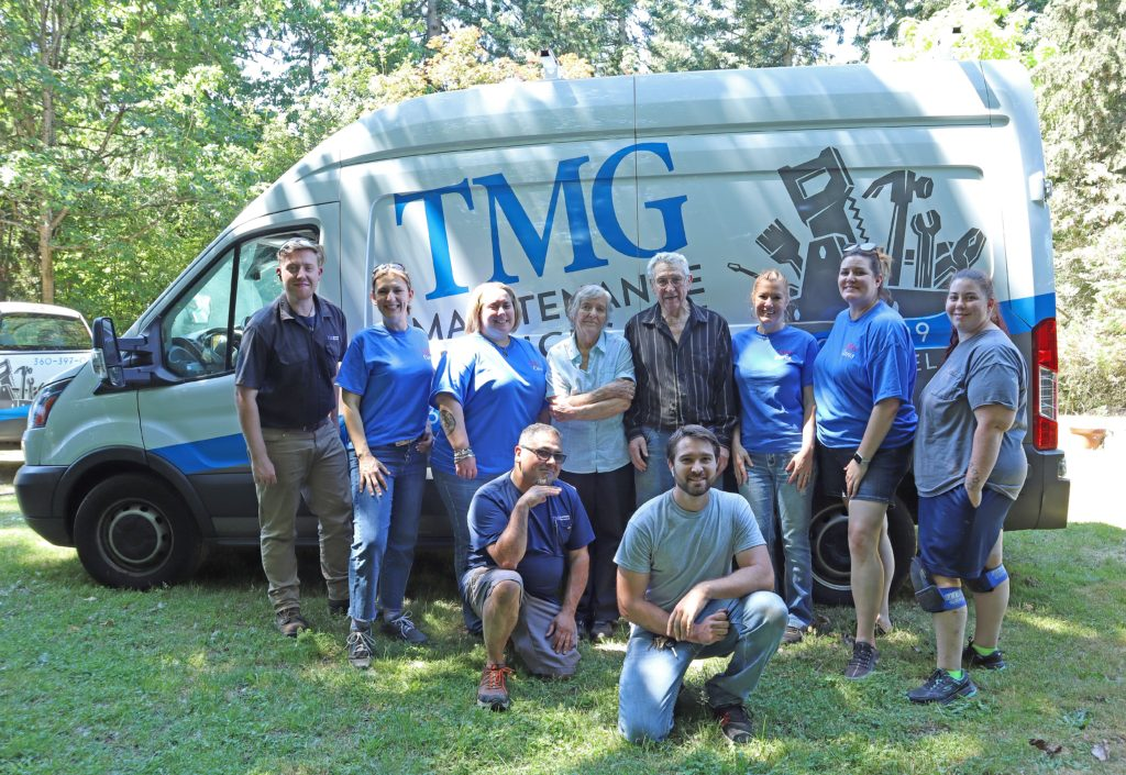 The volunteer team poses with the veteran and his family in front of a company van.