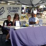Three people sitting at the Los Banos Chamber table
