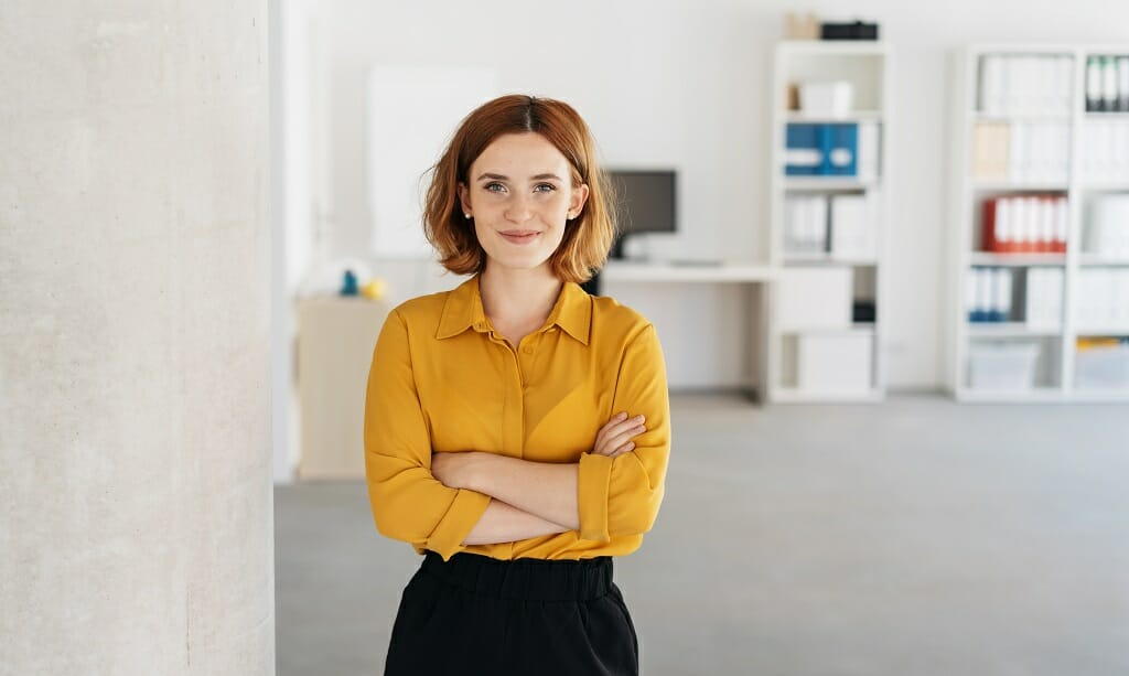 Happy relaxed confident young businesswoman standing with folded arms in a spacious office looking at the camera with a warm friendly smile