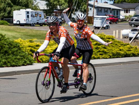 Tandem bikers waving