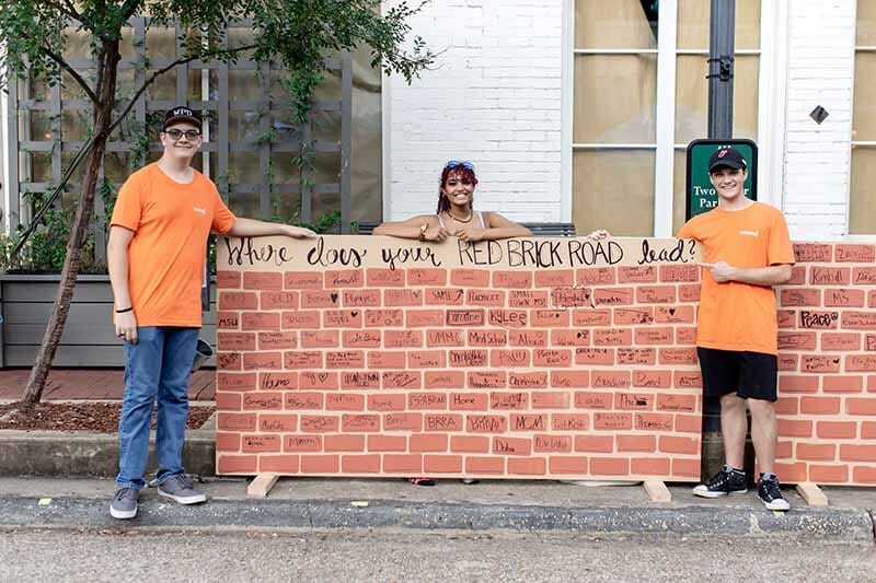"""Three youth volunteers managing an activity board that asks, """"Where does your Red Brick Road lead?"""""""