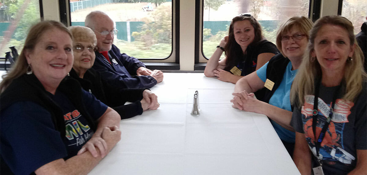 Six people sitting at a table near windows on a train.
