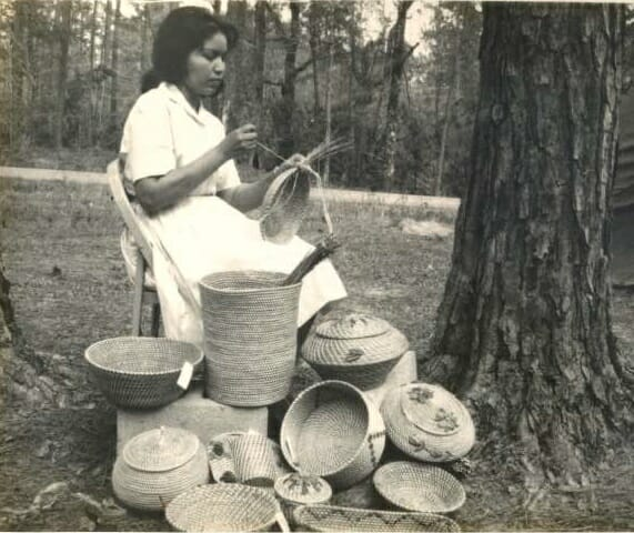 Ena Mae Sickey poses for a photo sewing a pine needle basket in front of a large collection of pine needle baskets, c. 1960s. Images may not be reproduced or used in any way without the express written permission of the Coushatta Tribe of Louisiana Tribal Archives.