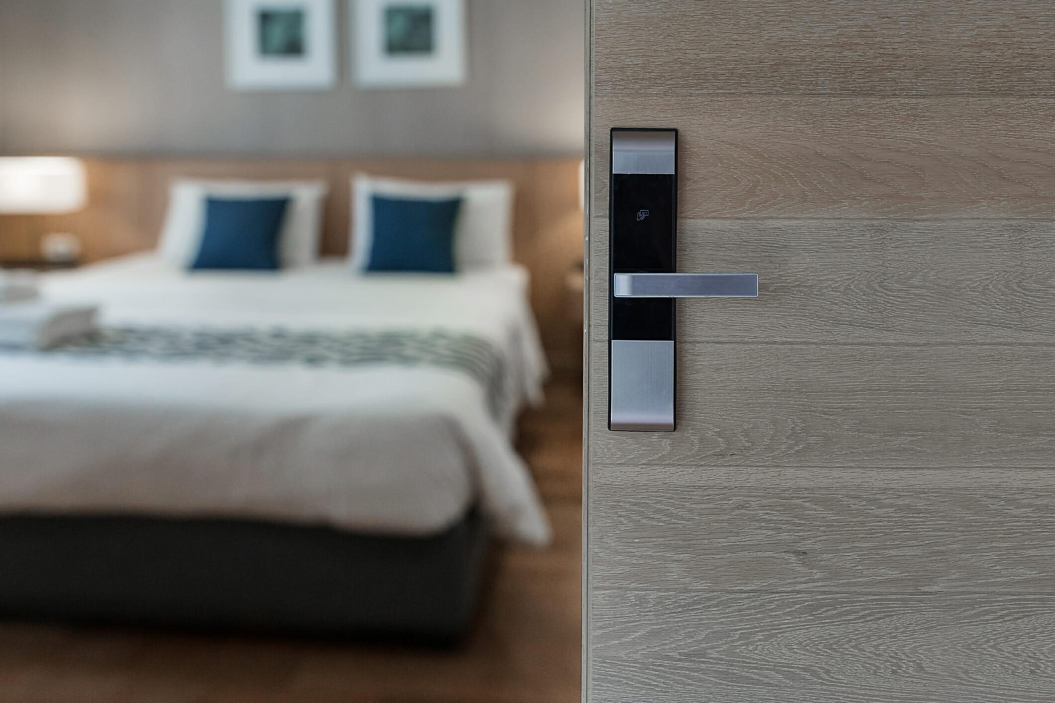 Hotel room , Condominium or apartment doorway with open door in front of blur bedroom background
