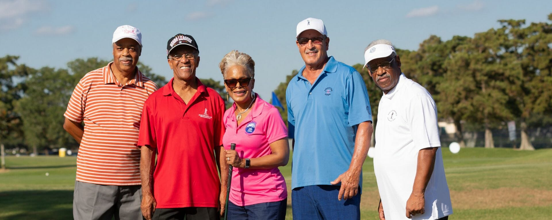 group smiling at camera at golf tournament