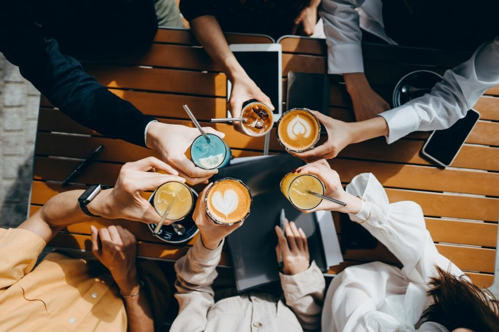 Top angle view of a group of corporate co-workers having drinks with reusable stainless steel straws and celebrating after work