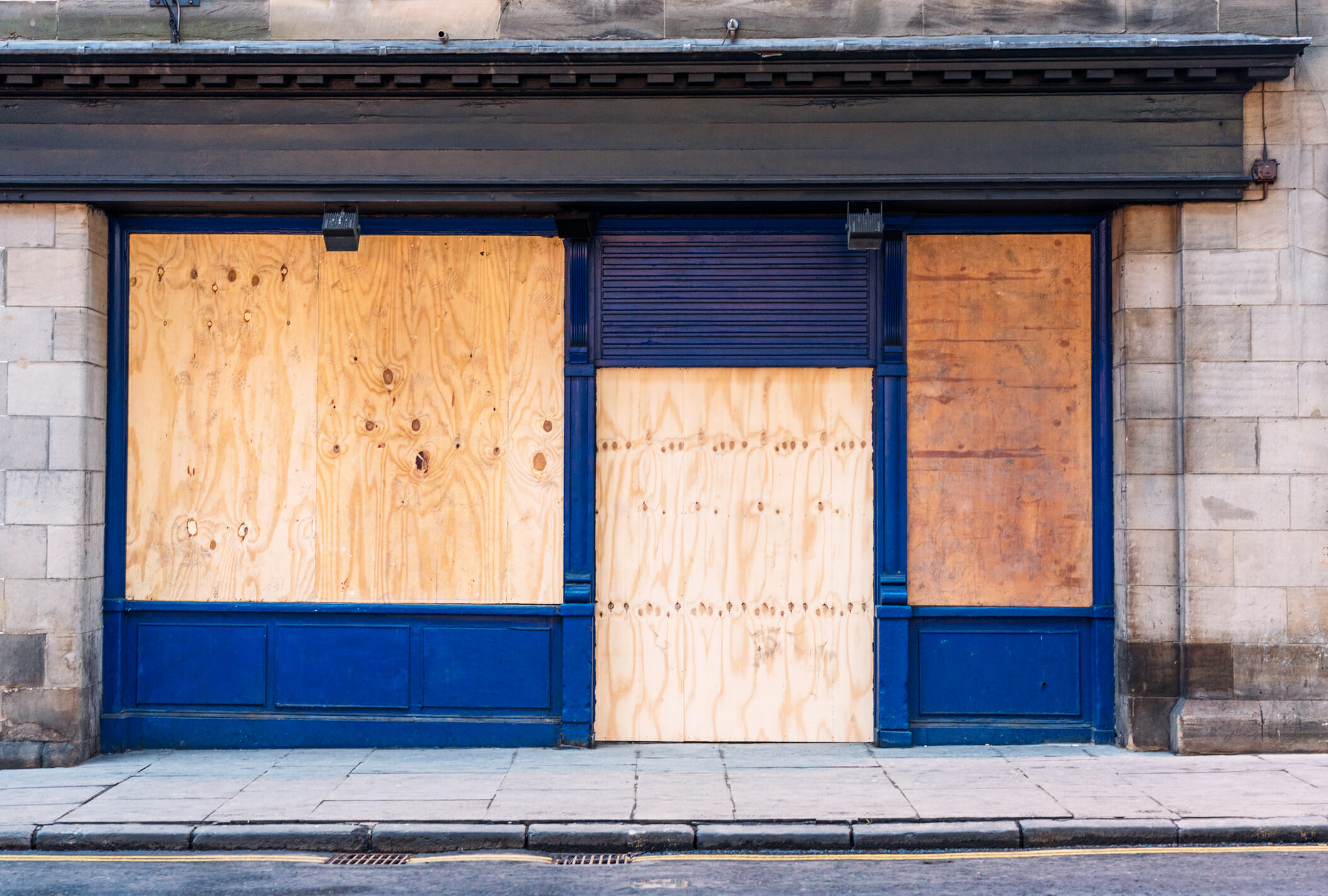 A traditional shopfront, closed and boarded up with wooden boards.
