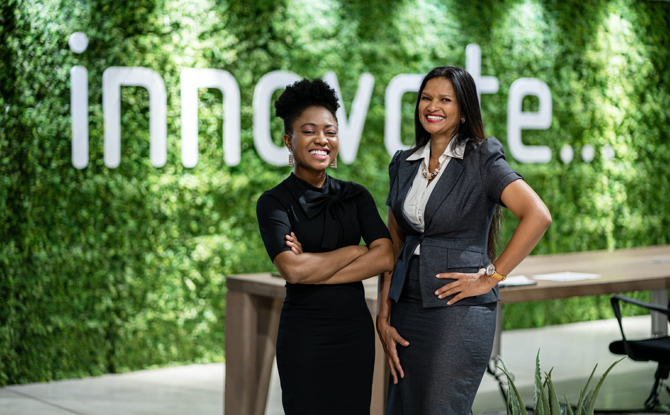 Portrait of a diverse young African business woman smiling while standing together in an eco-friendly modern office space
