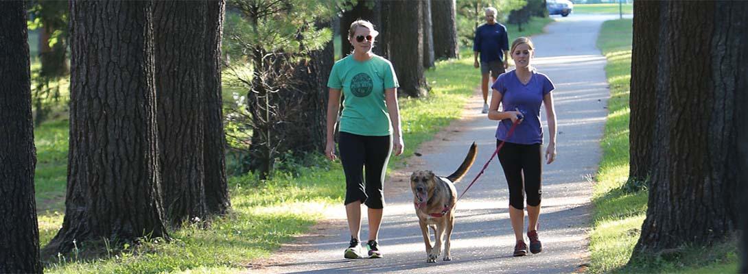 2 women walking a dog in the park