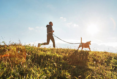 man and dog jogging along a grassy hilltop