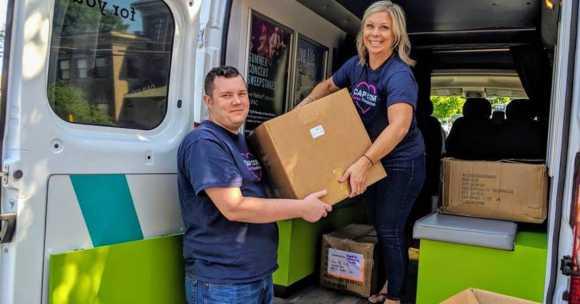 2 adult volunteers lifting cardboard boxed out of van