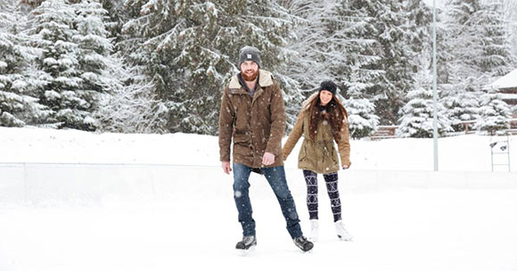 young man and woman skating outside with snowy backdrop
