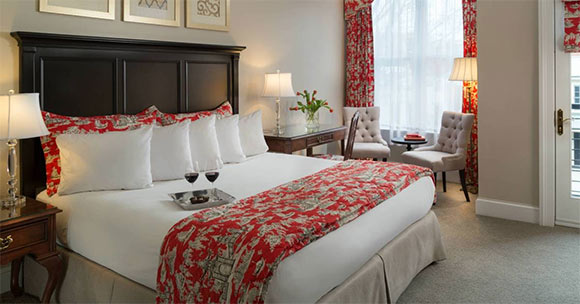 luxurious hotel room with wine glasses on the bed and fresh flowers