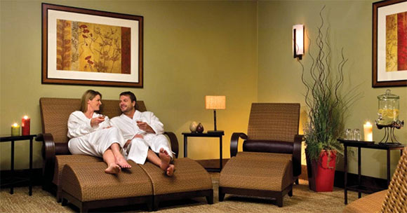 man and woman relaxing on spa lounges