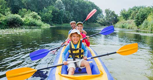 Boy with his sister and father having fun together enjoying adventurous experience kayaking on the river on a sunny day during summer vacation