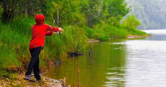 Boy fishing on a stream