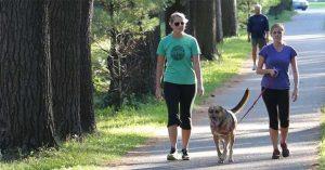 2 women walking dog in a park