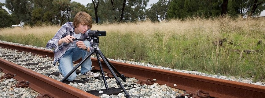 A teen making a film shooting outdoors using video camera and tripod.