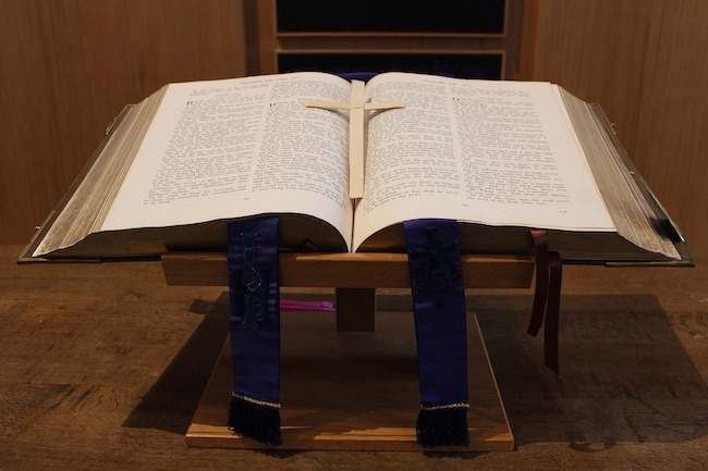Leadership-Preaching - Bible open on a stand with a cross in the middle of the bible