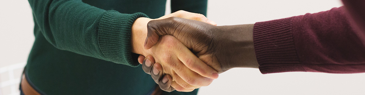 Two people with different color skin shake hands