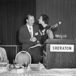 Charles Bourne (President) receiving kiss from Pauline Atherton (incoming President). Eugene Garfield on left; Mel Weinstock on right