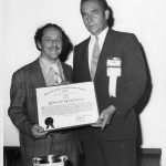 Eugene Garfield (l) receiving 1975 Award of Merit from Dale Baker (r)