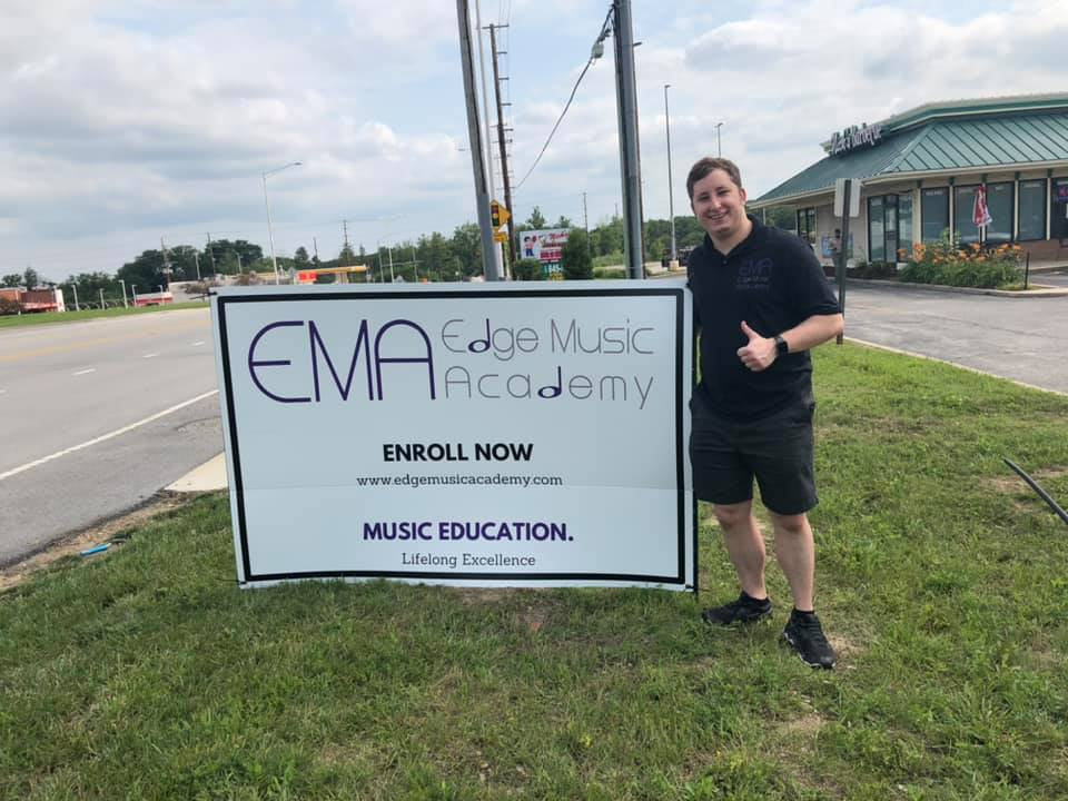 Owner Jason standing next to Edge Music Academy sign near street