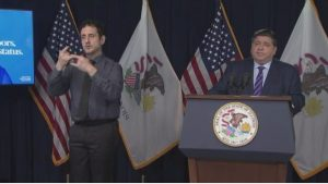 Govenor Pritzker speaking at podium with interpreter