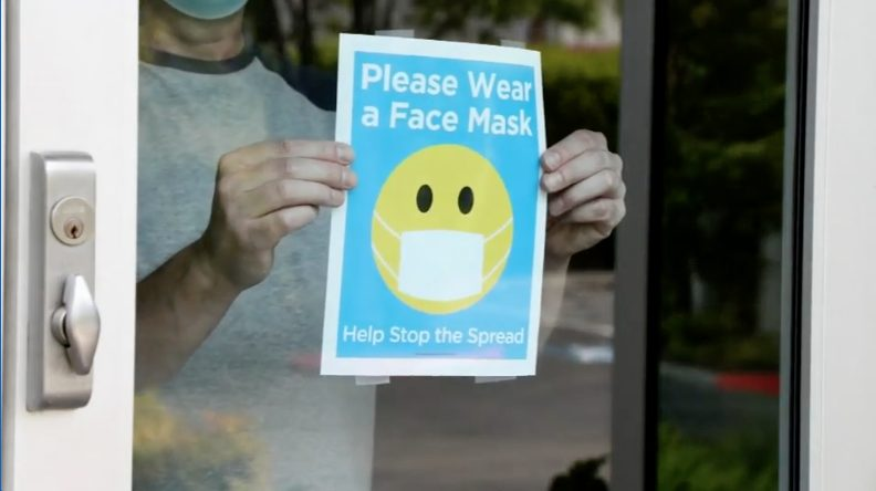 Storeowner putting a Wear a Face Mask sign on window